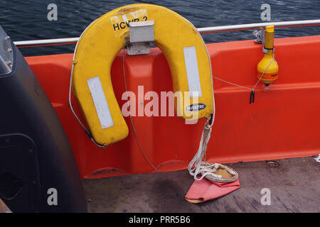 A picture of a yellow, horseshoe, buoyancy aid, life jacket, resting on a metal hook on the inside of a deck of a small sea going boat - Stock Image