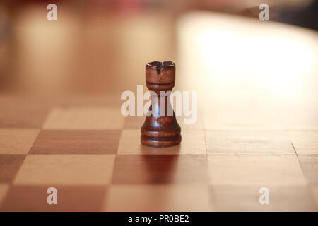 Wooden castle chess piece on a wooden chess board. - Stock Image