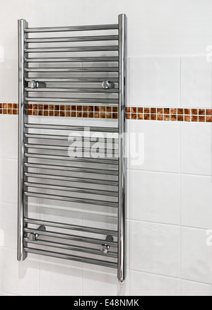 Chrome heated towel rail which serves a dual purpose as a radiator and towel dryer in modern bathrooms. - Stock Image