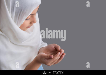 Young Muslim girl praying with eyes closed - Stock Image