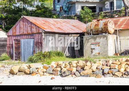 Corrugated hut with oil storage drum, beach by Pambula river estuary, New South Wales, Australia - Stock Image