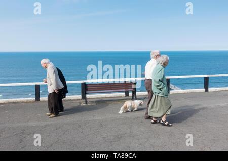 Elderly couples walking along promenade overloking the sea. UK - Stock Image