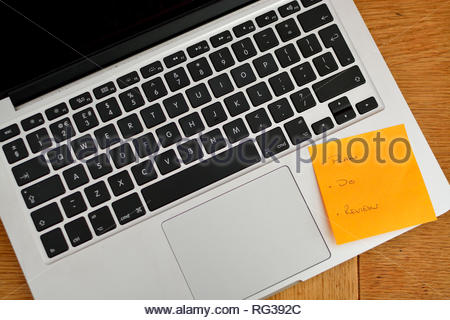 Flat lay style image of modern laptop computer keyboard. Orange sticky note stuck to the computer on a brown wooden desk. - Stock Image