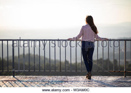 Beautiful woman back shot on a viewpoint railing with blurred background and copy space - Stock Image