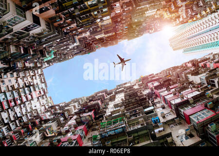 Plane flying dramatically overhead in Hong Kong's old densely residential housing district of Quarry Bay with deliberate lens flare. - Stock Image