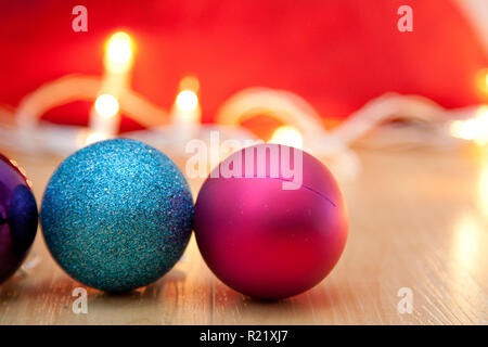 Pink and sparkly blue christmas ornaments with white lights - Stock Image