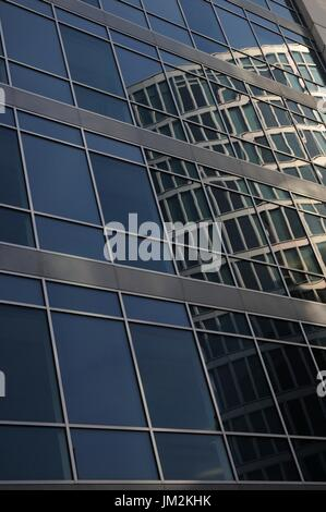Modern office block reflected in the steel and glass façade of other offices. - Stock Image