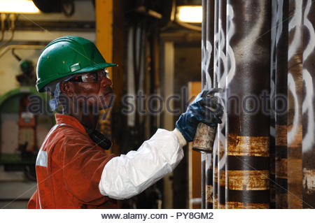 Worker wearing hard hat spray painting pipe - Stock Image