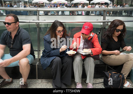Women shared food at Dine Around Downtown, an annual festival during which Lower Manhattan restaurants sell discounted samples from their menus. - Stock Image
