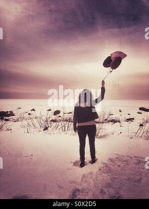 Girl on the edge of a frozen beach with balloons. - Stock Image