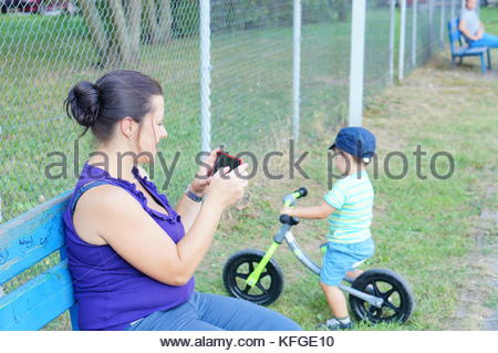 Woman taking a photo of her child on a balance bike with her smartphone while sitting on a bench in Poznan, Poland - Stock Image