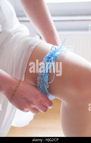 Bride,leg,knee,garter,blue,pantyhose,woman,wedding dress,standing,preparation,preparations,wedding,wedding day,wedding - Stock Image