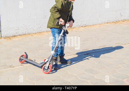 Boy TEENAGER riding a scooter in the city, the CHILD goes in for sports in the open spring. - Stock Image