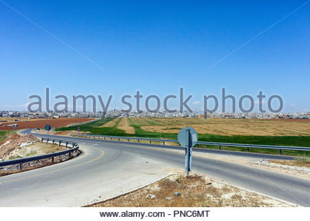 Road, highway to Amman Jordan - agriculture with plowed farming field - Stock Image