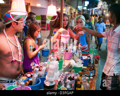 People buying buckets of alcoholic drinks at the Full Moon Party Haad Rin Koh Phangan Thailand - Stock Image
