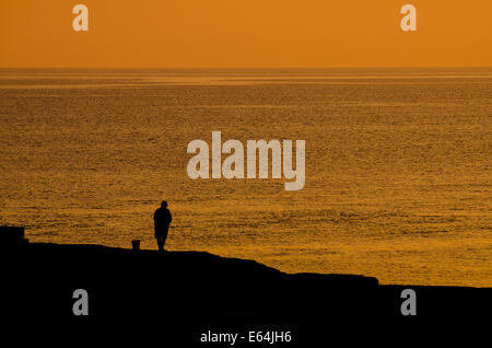 Silhouette of mature male  fisherman on rocks against a warm seascape at dawn. - Stock Image