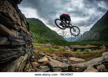 Man jumps a mountain bike through an abondoned iron works on a trail below the Gorza Canyon in Lyngenfjord in Norway. - Stock Image