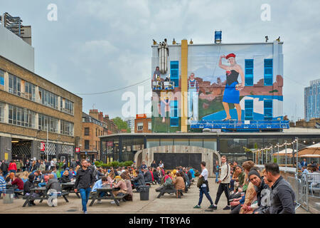LONDON ENGLAND BRICK LANE OPEN AIR EATING AREA AND PAINTERS PAINTING PICTURE ON A WALL FOR GUCCI - Stock Image