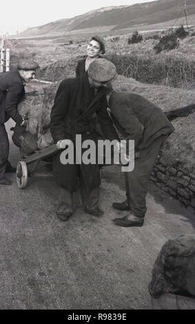 1940s, historical, unemployed Welsh miners outside on a path by a hillside, one of the men is pulling a wooden two-wheeled handcart with sacks of discarded coal they have collected from a nearby slag heap, Merthyr, Wales, UK - Stock Image