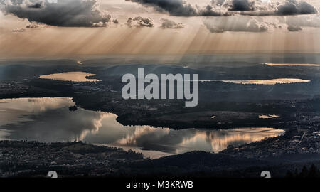 rays of sun in the clouds above the lakes of the province of Varese in winter season - Stock Image