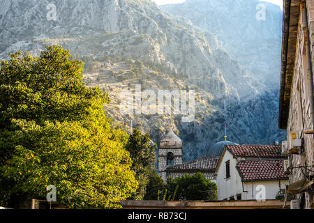 Mountains rise above the belfry of Saint Claire Church with the dome of the St. Nicholas church alongside in the ancient old town of Kotor, Montenegro - Stock Image
