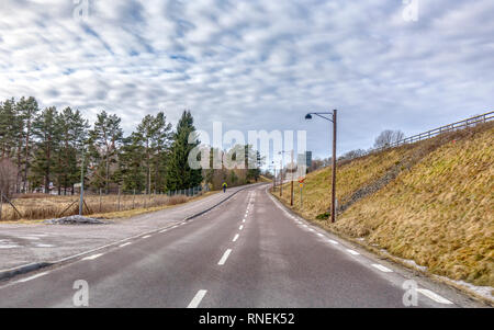 Two lane road or highway aka single carriageway with cyclist on bicycle lane or pedestrian sidewalk up ahead - Stock Image