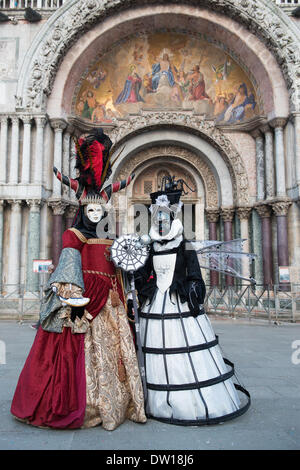 Venice, Italy. 25th Feb, 2014. Two costumed Carnivale revellers are pictured full length in front of the Basilica San Marco. (St Marks Basicilia). Venice Carnivale - Tuesday 25th February. Credit:  MeonStock/Alamy Live News - Stock Image