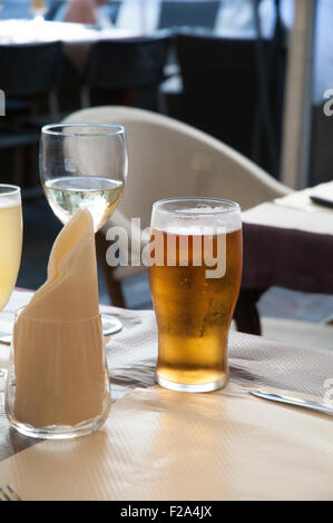 Pint of beer and a glass of wine sitting on a table. - Stock Image