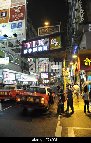 NIght time street scene, with family boarding taxi. Kowloon, Hong Kong, China - Stock Image