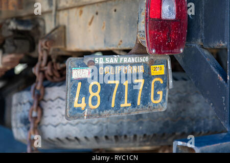 So. San Francisco California, license plate underneath a rusty old truck - Stock Image