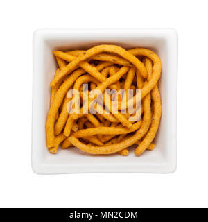 Pieces of muruku in a square bowl isolated on white background - Stock Image