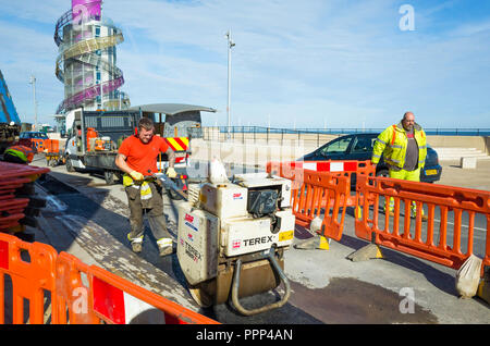 Road repairs on Redcar Seafront with a workman operating a hand controlled power roller compacting tarmac over a refilled cable trench - Stock Image