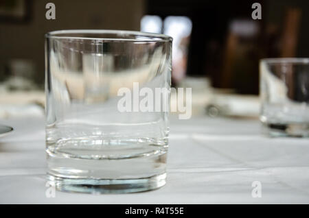 Empty tumbler drinking glasses on a table coverd with a white tablecloth - Stock Image