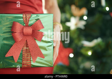 Closeup on green Christmas present box in a hands of woman in red dress near Christmas tree - Stock Image