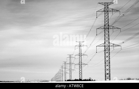 String of Powerline Towers Disappear into a Winter Horizon - Stock Image
