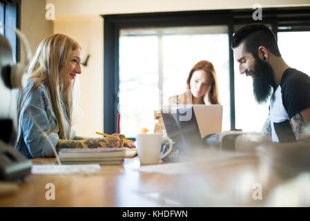 Colleagues working in casual office - Stock Image