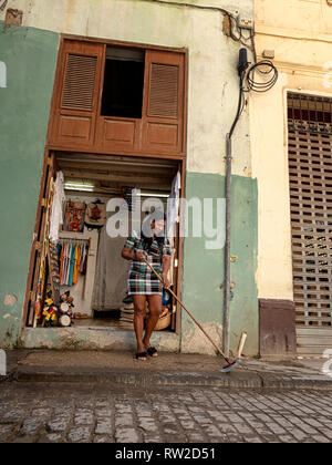 A woman sweeps the pavement outside her shop selling trinkets in Havana, Cuba - Stock Image