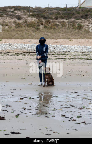 France, 2018, A girl stands with her dog on the beach., dressed against the cold and wind. - Stock Image