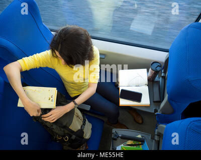 young attractive woman loking in backpack and packing during her traveling train - Stock Image