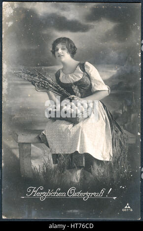A postcard printed in Germany, shows a rural landscape, a girl with a basket of eggs and sprigs of willow. The inscription - Stock Image