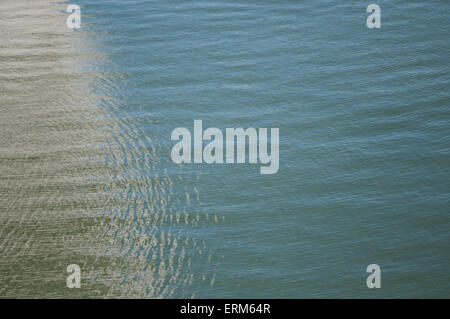 Interplay of light and shadows on water in the harbour. - Stock Image