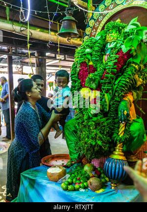 Parents Introducing Son to Hanuman Shrine, Sree Veera Hanuman Hindu Temple, Kuala Lumpur, Malaysia. - Stock Image