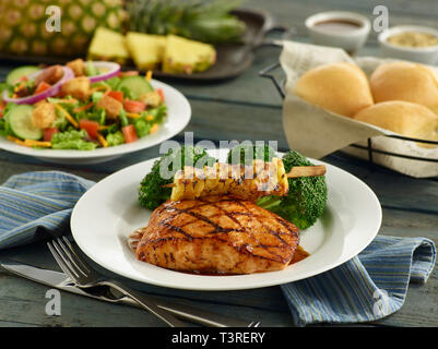 Glazed salmon filet with grilled pineapple, broccoli, salad and dinner rolls - Stock Image