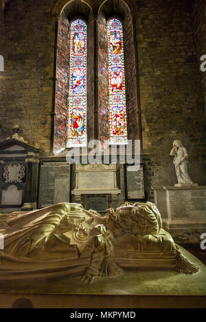 A sarcophagus tomb overlooked by a stained glass window in the medieval St.Canice's Cathedral (Chuch of Ireland / Anglican), Kilkenny, Ireland - Stock Image