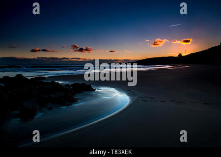Quiet and relaxed scenic beach place during dusk sunset with coloured sky in background - sea shore outdoor vacation concept - freedom and lifestyle n - Stock Image