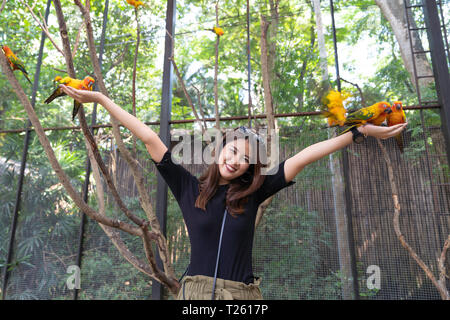 Asian beautiful woman enjoying with love bird on hand and body, in cage background, nature travel concept. - Stock Image