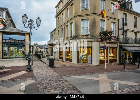 Shops and the office de tourisme along the main road through the medieval town of Bayeux in the Normandy region - Stock Image