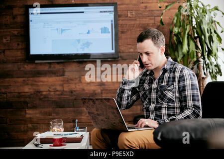 Man using a mobile phone using laptop sitting on sofa in a small office. - Stock Image