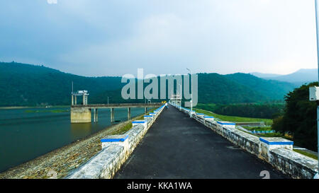 Road to Large Dam and water reservoir between blue mountains and thick forest with pure nature - Stock Image