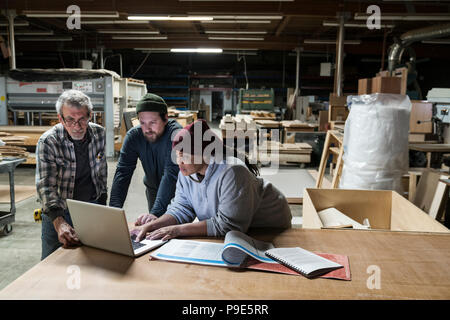 Three mixed race carpenters workng on a laptop computer after work hours in a large woodworking factory. - Stock Image